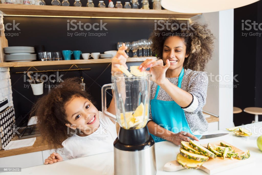 Beautiful African American woman and her daughter cutting fruit in the kitchen stock photo