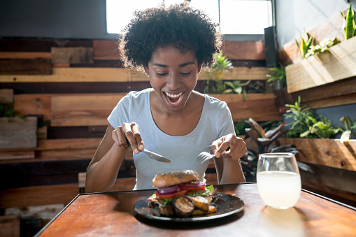 Beautiful african american woman eating a delicious bagel with vegetables at a restaurant looking happy and very hungry