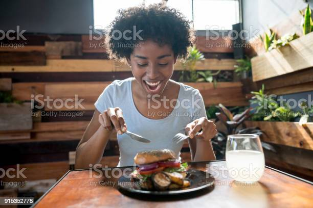 Beautiful african american woman eating a delicious bagel with picture id915352778?b=1&k=6&m=915352778&s=612x612&h=8b8zzxzyqjkkh0puim0b juhvvhuvpcb1qyftt8pk2w=