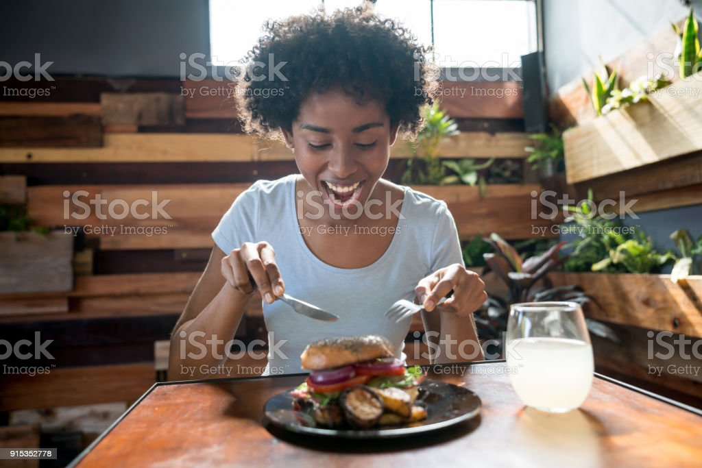 Beautiful african american woman eating a delicious bagel with vegetables stock photo