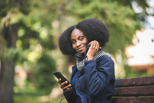Beautiful African American Woman Getting Ready to Listen To A Podcast On Her Mobile Device, In A Public Park stock photo