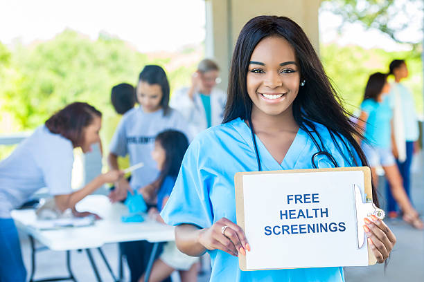 "beautiful african american woman holding a """"free health screenings"""" sign - screening stock photos and pictures"