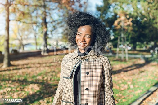Beautiful African American young woman with afro hairstyle in a stylish coat in a park, smiling. Fall season and lifestyle concept