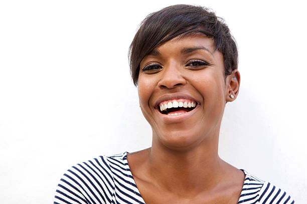 Beautiful african american woman laughing Close up portrait of a beautiful african american woman laughing on white background short hair stock pictures, royalty-free photos & images