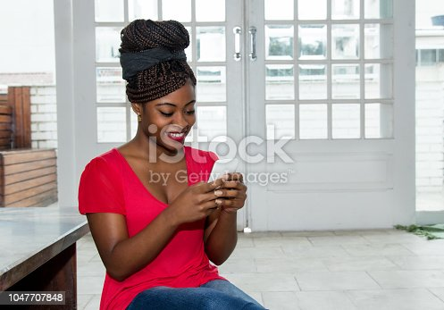 istock Beautiful african american woman sending message with phone 1047707848