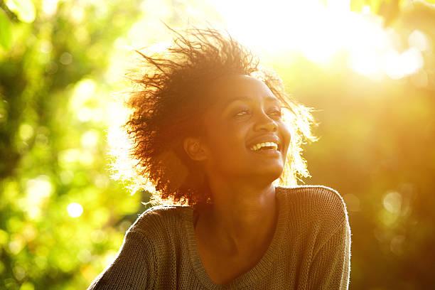 schöne afroamerikanische frau, lächeln mit sonnenuntergang - dynamische posen stock-fotos und bilder