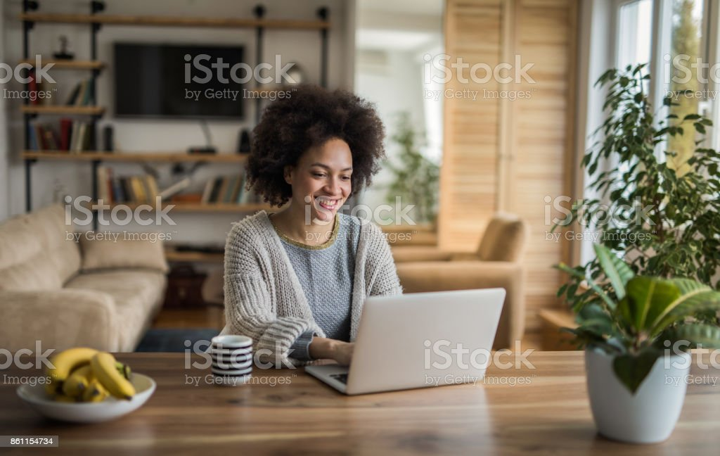Beautiful African American woman typing an e-mail on laptop at home. stock photo