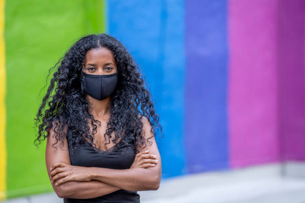 Beautiful African American Woman Wearing a Protective Face Mask Woman in her 20s wearing a protective face mask to protect herself from the transfer of germs during COVID-19 outbreak, standing in front of a pride mural. social justice concept stock pictures, royalty-free photos & images