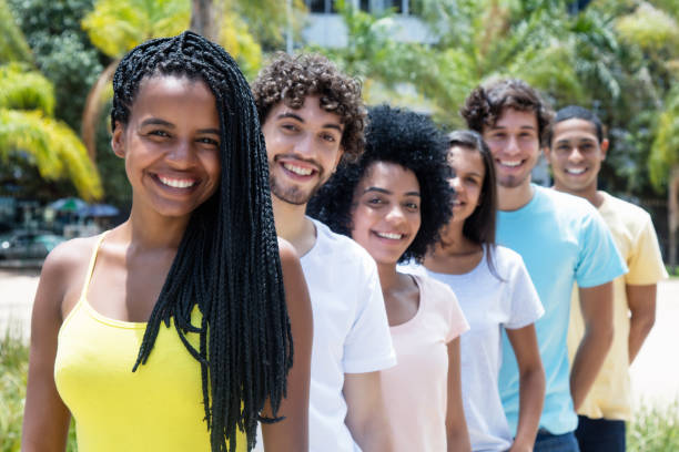 Beautiful african american woman with dreadlocks with multi ethnic friends in line stock photo