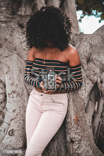 Beautiful young woman in a 60's-70's themed image uses a retro old fashioned camera outdoors in a park like location. She is cool and hip and could be from any decade. Photography and vintage retro themed image