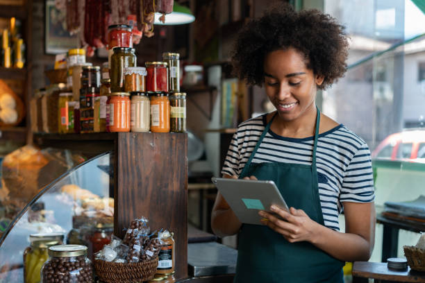 beautiful african american woman working at a delicatessen looking at orders for delivery on tablet smiling - small business owner stock pictures, royalty-free photos & images