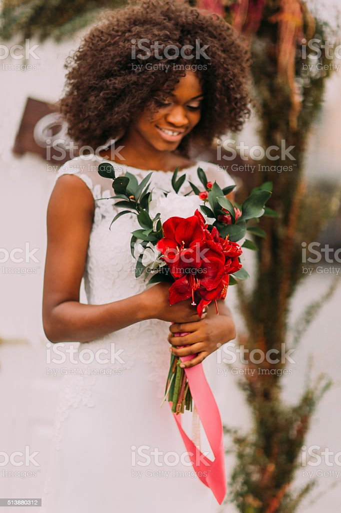 Beautiful african bride happily smiling with bouquet of red flowers stock photo