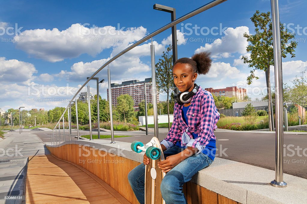 Beautiful African girl holds skateboard and sits stock photo