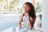 Beautiful african girl with skin problems and sits in a cafe for a cup of hot tea Vitiligo