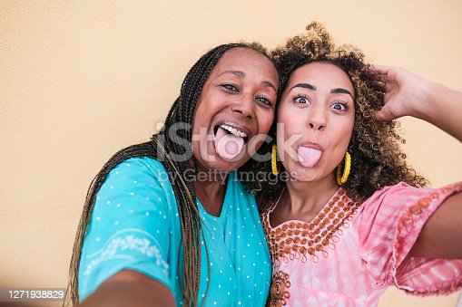 istock Beautiful african mother and adult daughter stick their tongue out while they take a selfie - Family love 1271938829