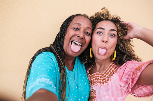 Beautiful african mother and adult daughter stick their tongue out while they take a selfie - Family love