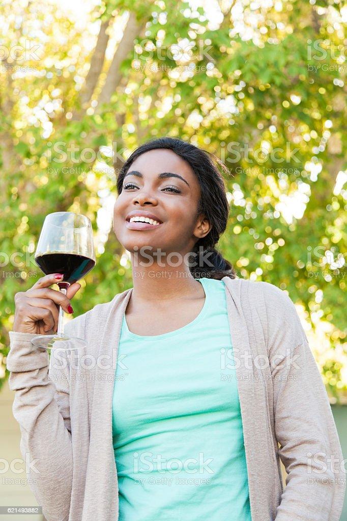 Beautiful african woman having a glass of wine. photo libre de droits