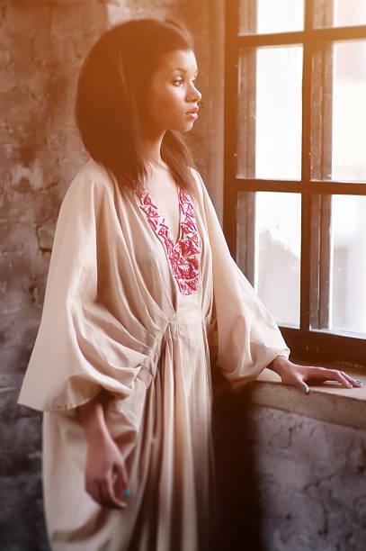 Beautiful african woman in dress near the window stock photo