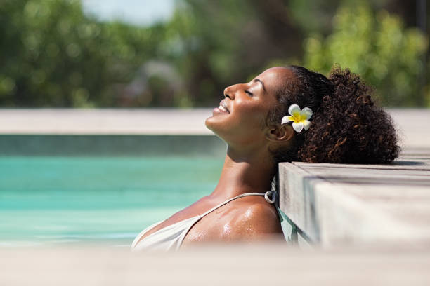 Beautiful african woman in pool relaxing Young black woman relaxing at spa pool with frangipane flower in the hair. Beautiful young woman relaxing in outdoor spa swimming pool with head leaning at poolside. Closeup face of attractive black girl with closed eyes enjoy vacation at resort. poolside stock pictures, royalty-free photos & images