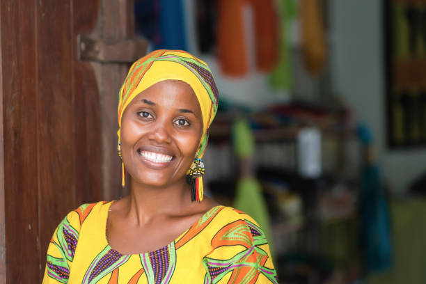 Beautiful African woman Young African woman in traditional clothes standing in entrance of her store, smiling at camera headscarf stock pictures, royalty-free photos & images