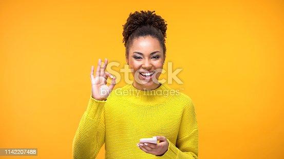 istock Beautiful african woman showing ok gesture, online shopping application, gadget 1142207488