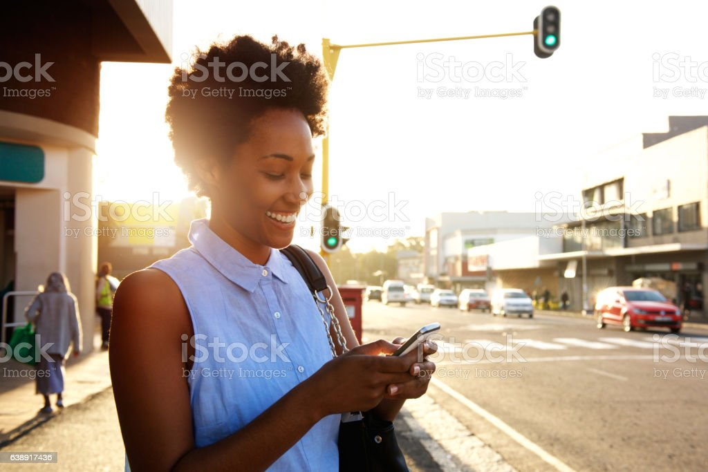 Beautiful african woman using cellphone outdoors stock photo