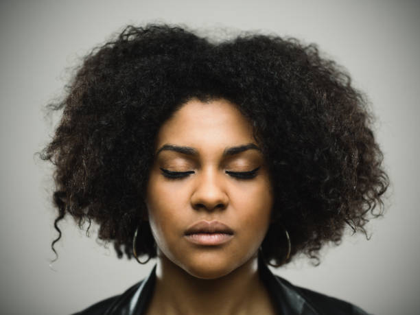Beautiful african woman with eyes closed Horizontal portrait of beautiful african woman with curly hair against gray background. Close-up of real young black woman with eyes closed. Studio photography from a DSLR camera. Sharp focus on eyes. eyes closed woman stock pictures, royalty-free photos & images