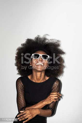 Elegant african woman in little black dress and sunglasses standing on white background.