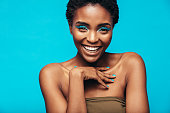 Close up of beautiful young african woman with vivid makeup smiling against blue background. Female model wearing artistic makeup looking at camera.