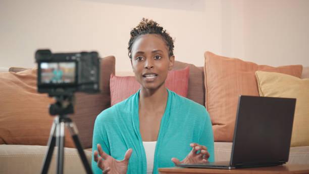 beautiful african-american vlogger recording livestream for her show - videocamera foto e immagini stock