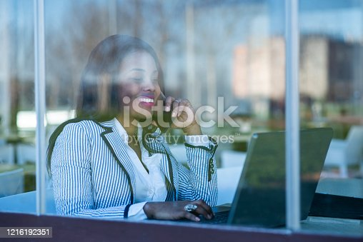 Beautiful African-American woman using a laptop and talking on her cell phone behind a window
