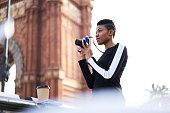 Beautiful afro American female photographer taking picture of cityscape strolling outdoors, attractive young creative hipster girl with short haircut going sightseeing making photos of notable places