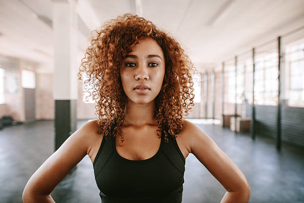 beautiful afro american female with curly hair in gym - brassière de sport photos et images de collection