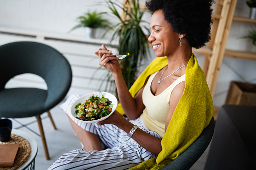Cheerful afro american woman eating fresh vegetable salad at home.