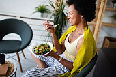 istock Beautiful afro american woman eating vegetable salad at home. 1276382999