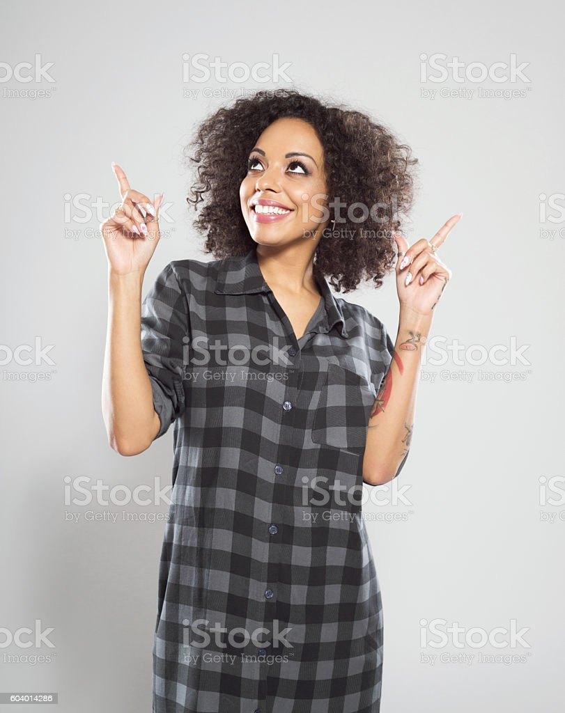 Beautiful afro american woman pointing at copy space Portrait of happy afro american young woman wearing casual checkered dress, standing against grey background and pointing with index fingers at the copy space. Adult Stock Photo