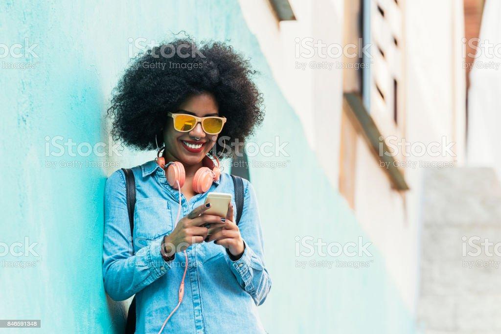 Belle femme afro américaine à l'aide de mobile dans la rue. - Photo