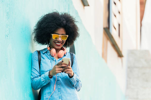 Beautiful afro american woman using mobile in the street. Beautiful afro american woman using mobile in the street. Communication concept. one young woman only stock pictures, royalty-free photos & images