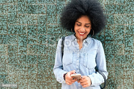 istock Beautiful afro american woman using mobile in the street. 846591350