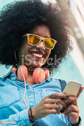 istock Beautiful afro american woman using mobile in the street. 846591352