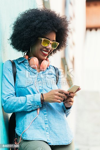 istock Beautiful afro american woman using mobile in the street. 846591366