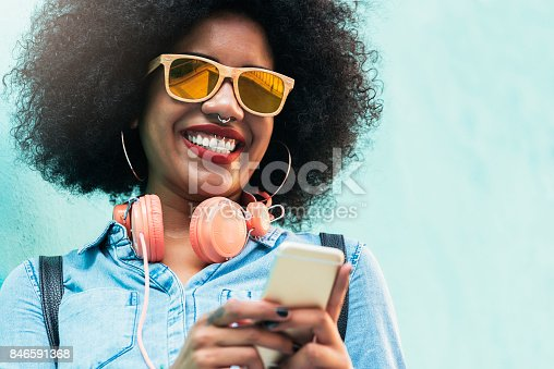 istock Beautiful afro american woman using mobile in the street. 846591368