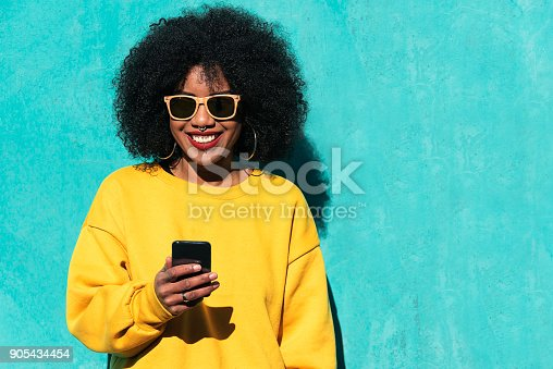 istock Beautiful afro american woman using mobile in the street. 905434454