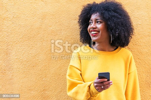 istock Beautiful afro american woman using mobile in the street. 905434496