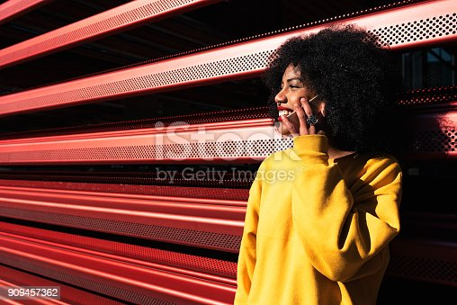 istock Beautiful afro american woman using mobile in the street. 909457362