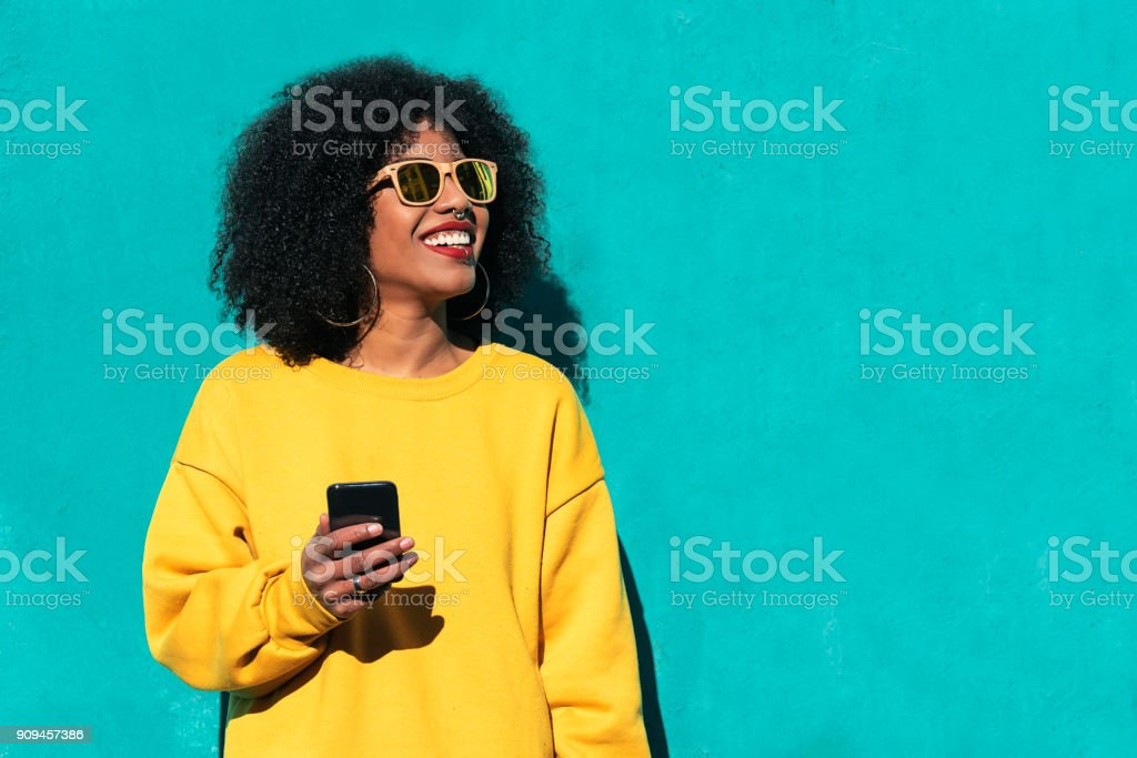 Beautiful afro american woman using mobile in the street. royalty-free stock photo