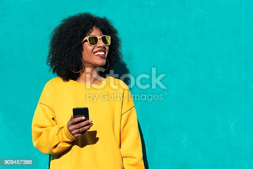 909457386istockphoto Beautiful afro american woman using mobile in the street. 909457386
