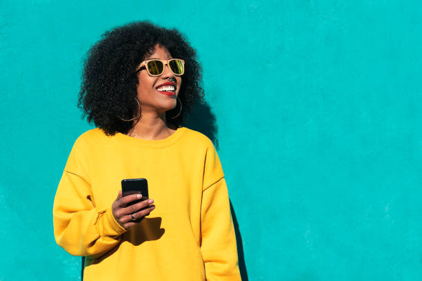 beautiful afro american woman using mobile in the street. - women stock pictures, royalty-free photos & images