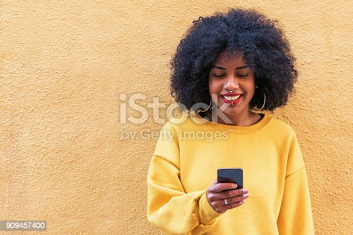 istock Beautiful afro american woman using mobile in the street. 909457400