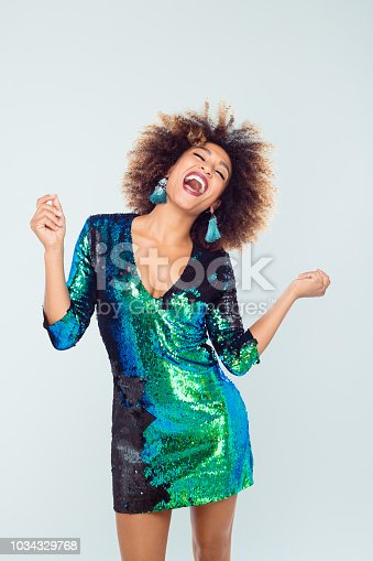 Portrait of beautiful afro american young woman wearing green shiny dress dancing against white background.